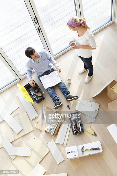 Couple surrounded by unassembled furniture