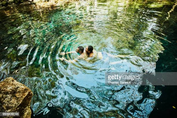 Couple swimming together while exploring cenote during vacation