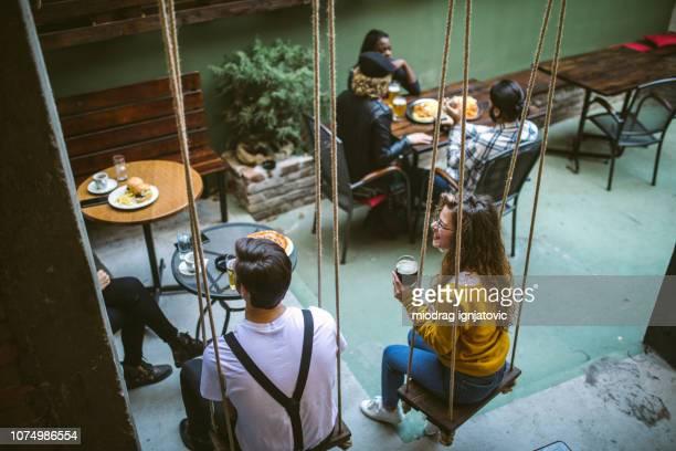 coppia che oscilla delicatamente mentre brinda con la birra - gruppo medio di persone foto e immagini stock