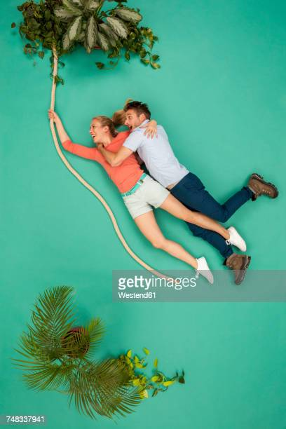 Couple swinging on a liana through the jungle