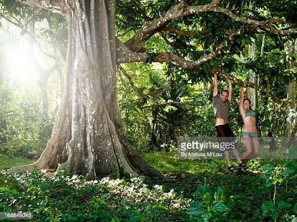 Couple swinging on banyan tree in Fiji