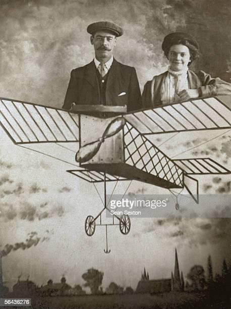 A couple take a flight of fancy on a cardboard cutout aeroplane circa 1910