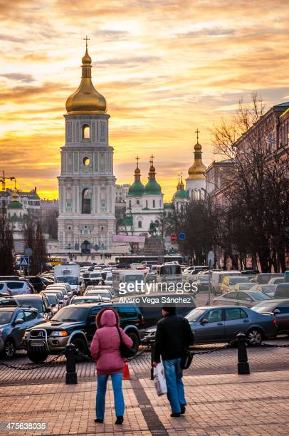 Couple take a healthy walk in front of a gigantic traffic jam and a beautiful sunset in central Kiev, Ukraine. At the end, the cathedral of St....