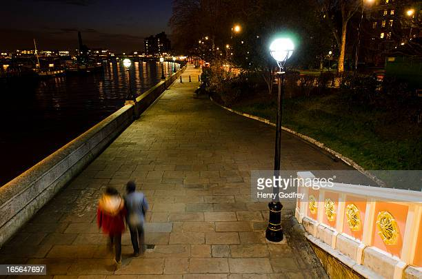 Couple take a late night stroll down Chelsea Embankment next to the Thames River.