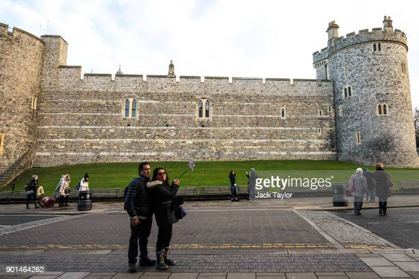 A couple take a photograph with a 'selfiestick' outside Windsor Castle on January 5 2018 in Windsor England British Prime Minister Theresa May has...