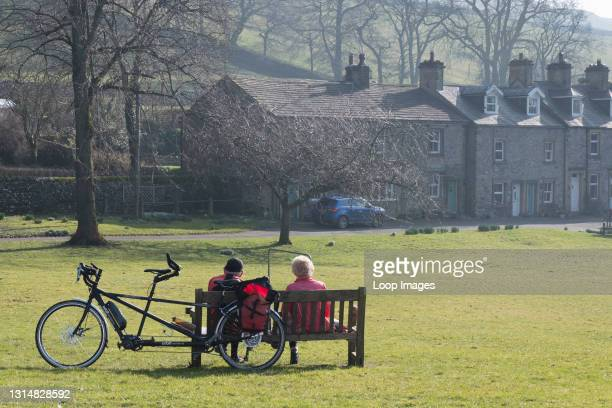 Couple take a rest from their tandem bike on a bench in Langcliffe in the Yorkshire Dales.