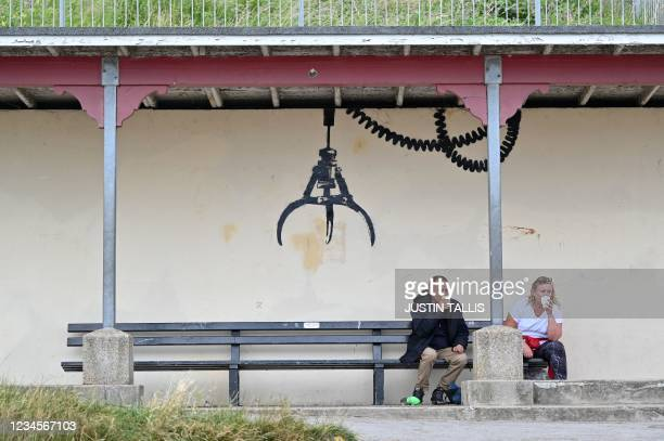 Couple take a rest on a bench below a graffiti artwork of an amusement arcade grabber, which bears the hallmarks of street artist Banksy, on a wall...