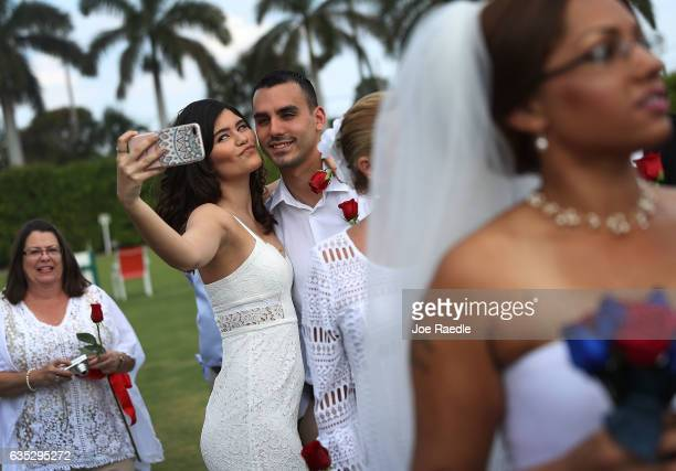 Andrea Rodriguez and Alejandro Gutierrez take a selfie picture as they participate in a group Valentine's day wedding ceremony at the National...