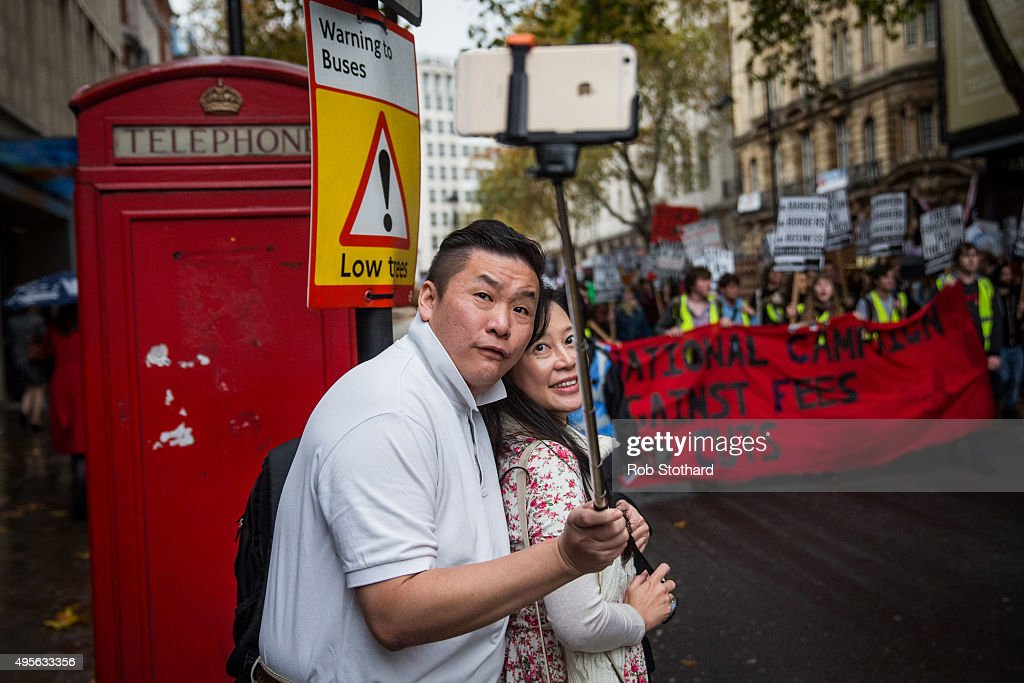 A couple take a selfie in front of a protest against education cuts and tuition fees on November 4, 2015 in London, England. University students from across the country are marching on the streets of London to protest against cuts to free education. After a rally outside what was the University of London Union, the march will take in Parliament Square, Millbank - occupied by student protesters five years ago - and end in front of the Department for Business, Innovation and Skills (the department responsible for universities).
