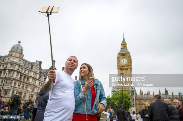 A couple take a selfie in Parliament Square London where onlookers have gathered as Big Ben's bongs ring out for the last time before renovation work...