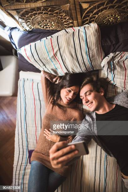 couple take a selfie lying down in the bed
