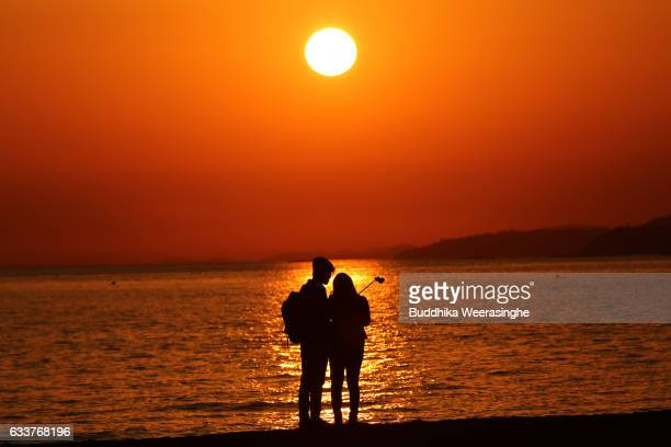 A couple take a selfie photo during sunset as they enjoy the first day of spring at the Shinmaiko beach on February 4 2017 in Tatsuno Hyogo...