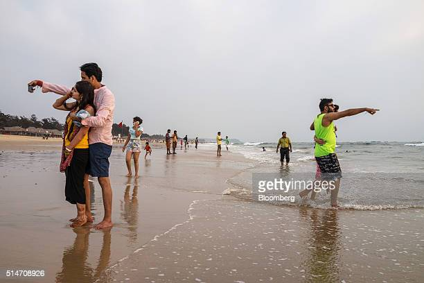 A couple take a selfie photograph as tourists and visitors gather at Baga beach in Bardez Goa India on Wednesday March 9 2016 While India is forecast...