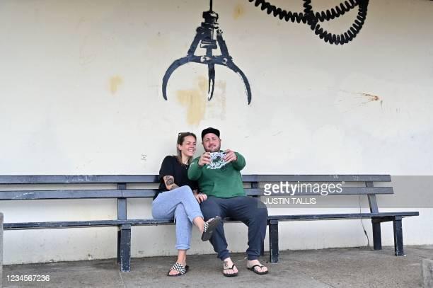 Couple take a selfie photograph below a graffiti artwork of an amusement arcade grabber, which bears the hallmarks of street artist Banksy, on a wall...