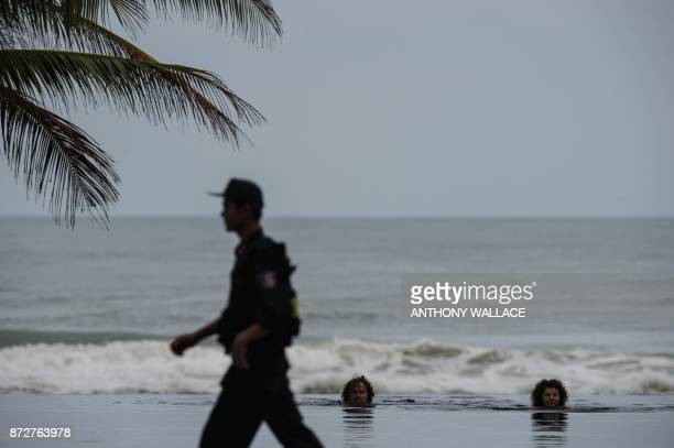 TOPSHOT A couple take a swim as a member of security patrols the grounds of a hotel before a press conference by Mexico's President Enrique Pena...