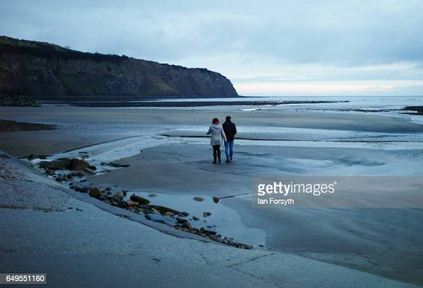 A couple take an early morning walk on the beach as day breaks over Robin Hood's Bay on the North Yorkshire coast on March 8 2017 in Robin Hood's Bay...