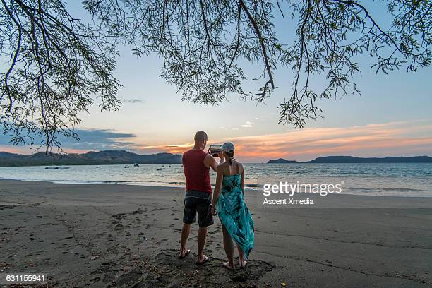 Couple take digital tablet pic from beach, sunrise
