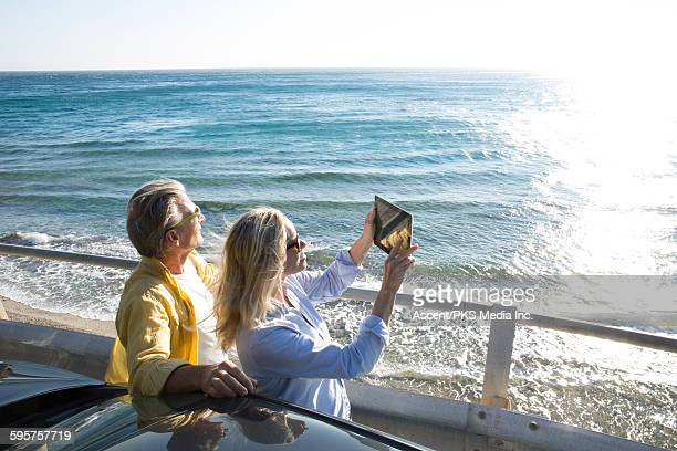 Couple take digital tablet pic from car,across sea