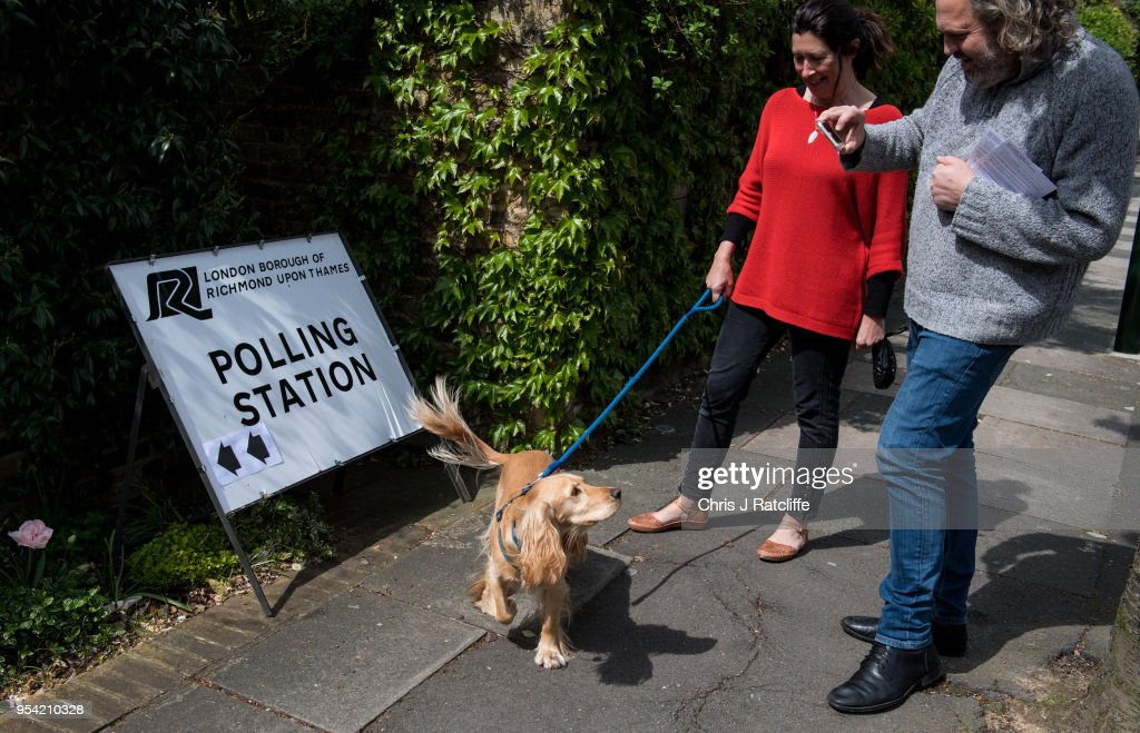 A couple take photos of their dog next to a polling station sign as they go to cast their votes at a station in a church in Twickenham on May 3, 2018 in London, England. Votes are being cast in more than 4,300 council areas in the biggest test for the political parties since the general election last year.