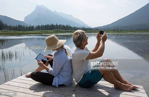 Couple take pic and use digital tablet, mtn lake