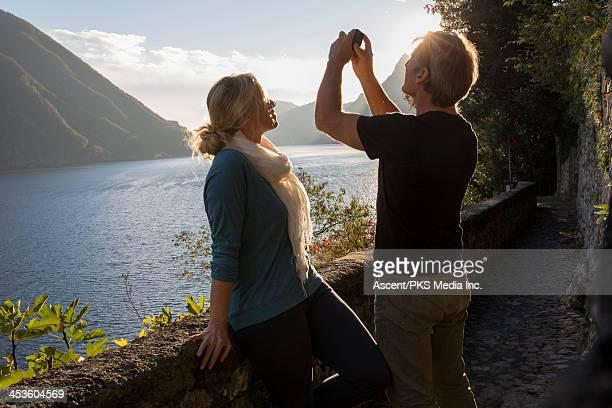 Couple take picture across lake, mountains