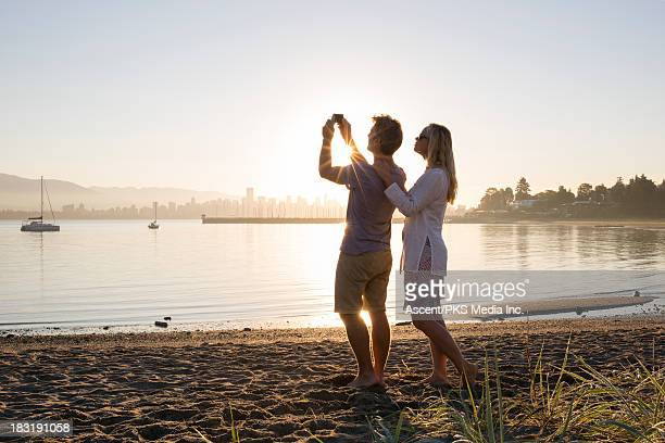 couple take picture from beach, of bay and skyline - vancouver skyline stock pictures, royalty-free photos & images
