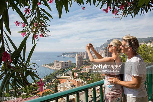 couple take picture over city and sea from balcony - monaco stock pictures, royalty-free photos & images
