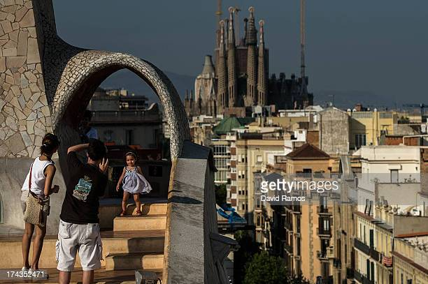 A couple take pictures of their daughter at the roof of the building 'La Pedrera' or 'Casa Mila' of Antoni Gaudi with La Sagrada Familia on the...