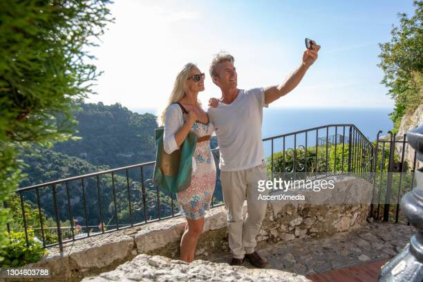 couple take selfie from balcony over the sea and forest - alpes maritimes stock pictures, royalty-free photos & images