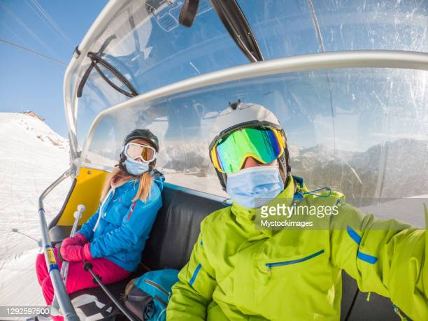 couple take selfie on ski lift, covid-19 - skiing stock pictures, royalty-free photos & images