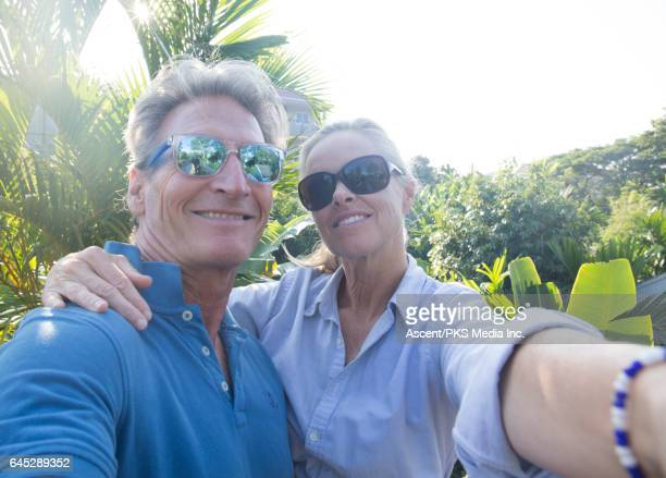 Couple take selfie pic in front on tropical vegetation