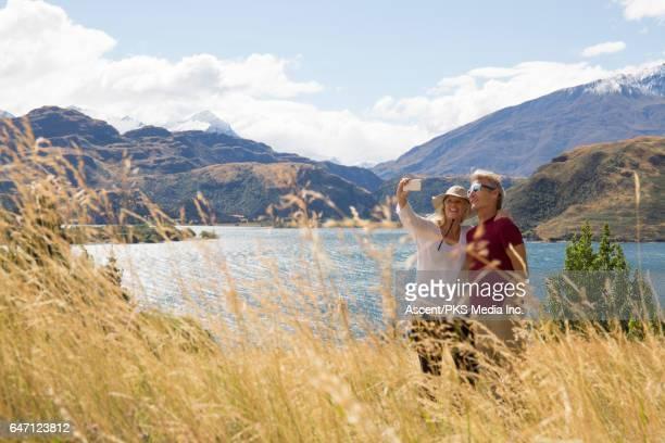 Couple take selfie pic on grass hillside above lake
