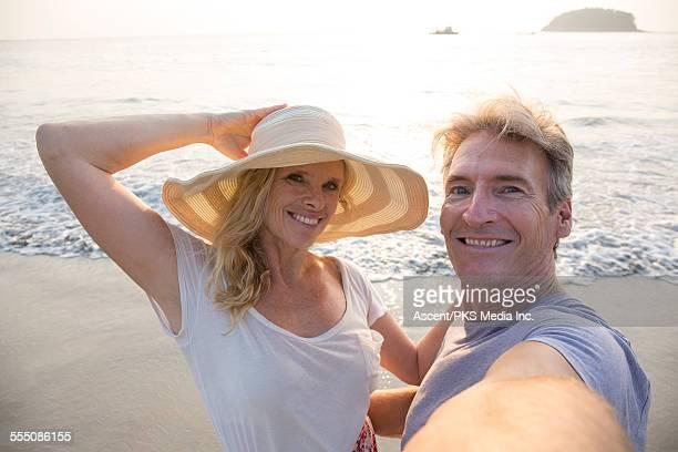 Couple take selfie portrait on beach, sunrise