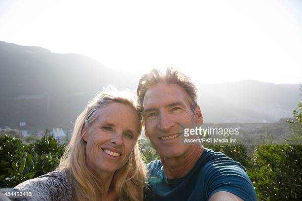 Couple take selfie portrait on hill, above oranges