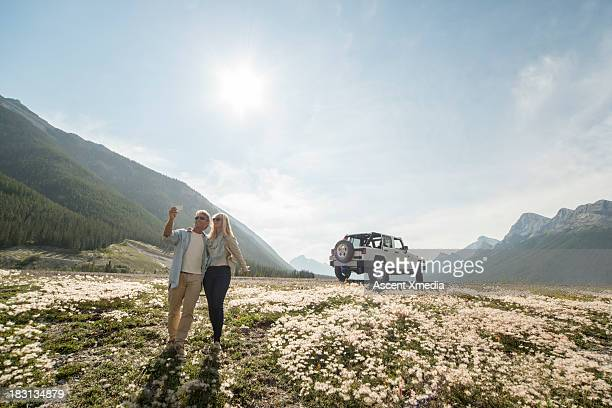 Couple take self-portrait snap, walking from Jeep