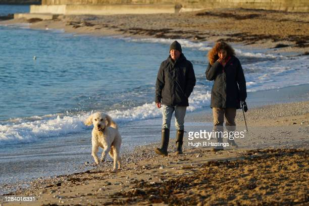 Couple take their exercise by walking their dog at Gyllyngvase Beach on November 5, 2020 in Falmouth, United Kingdom. England enters second national...
