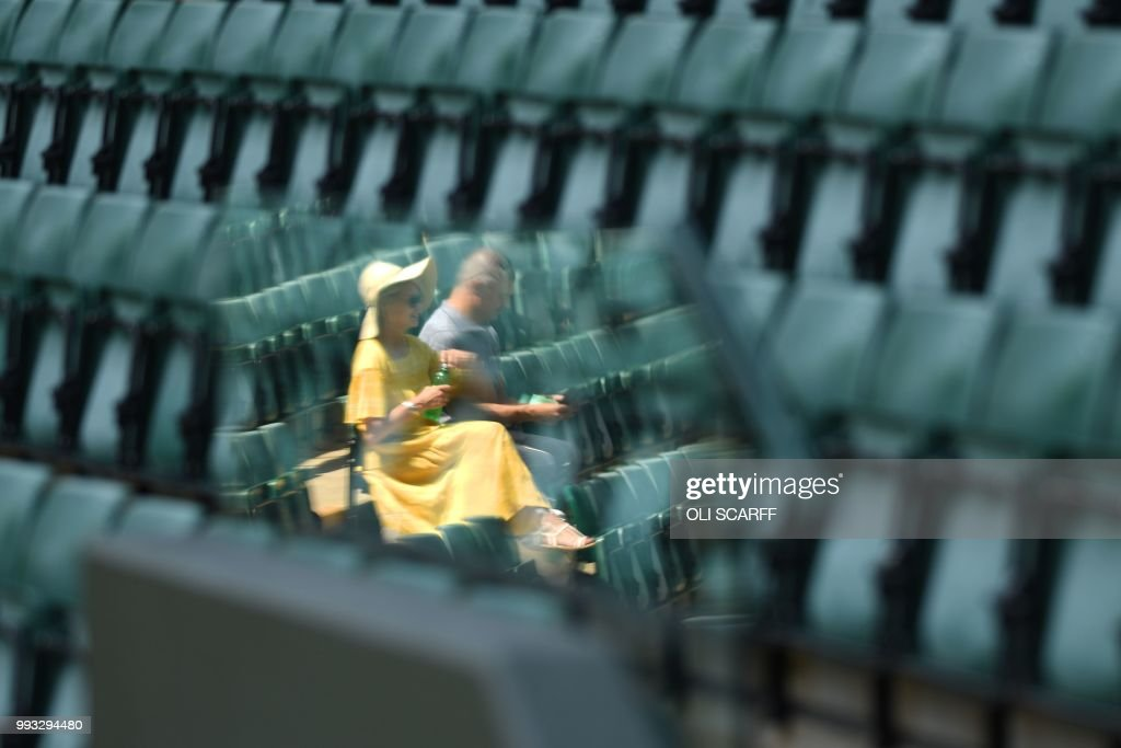 TOPSHOT - A couple take their seats on court 1 on the sixth day of the 2018 Wimbledon Championships at The All England Lawn Tennis Club in Wimbledon, southwest London, on July 7, 2018. (Photo by Oli SCARFF / AFP) / RESTRICTED