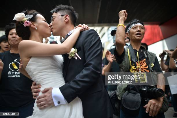 A couple take wedding photogtaphs in front of prodemocracy protesters in Hong Kong on October 1 2014 Hong Kong protesters who braved thunderstorms to...