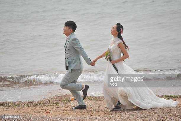 A couple take wedding photos by the sea at the Eight Great Passes on October 12 2016 in Qingdao Shandong Province of China Qingdao Eight Great Passes...