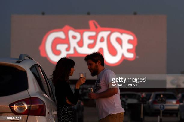 A couple takes a drink as they wait for the screening of the US musical romantic comedy film Grease during the reopening of the Autocine Madrid Race...