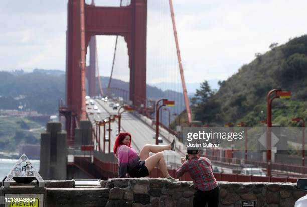 A couple takes a photo in front of the Golden Gate Bridge on March 17 2020 in San Francisco California Seven San Francisco Bay Area counties have...