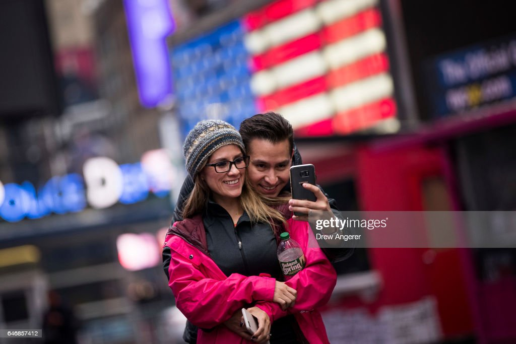 A couple takes a photograph of themselves in Times Square, March 1, 2017 in New York City. NYC & Company, the city's tourism marking agency, released a new forecast on Tuesday predicting 300,000 fewer foreign visitors this year. According to NYC & Co., the recent travel ban and related rhetoric from President Donald Trump has stunted interest in international tourism.