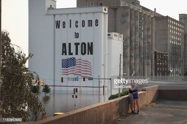 A couple takes a picture on a building overlooking an area flooded by the Mississippi River near the historic downtown on May 31 2019 in Alton...