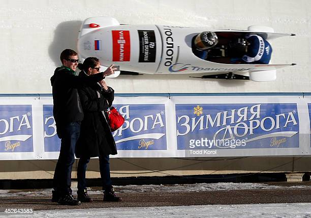 A couple takes a self portrait in front of Olga Stulneva and Liudmila Udobkina of Russia in the women's bobsleigh first run during the 2013 IBSF...