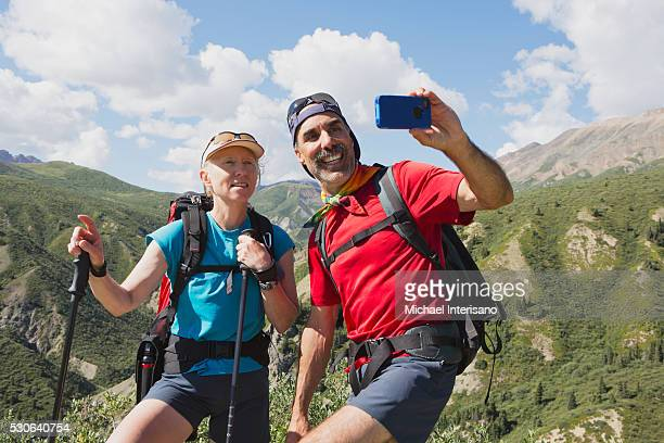 A couple takes a self portrait with a cell phone camera in the mountains; Haines Junction, Yukon, Canada