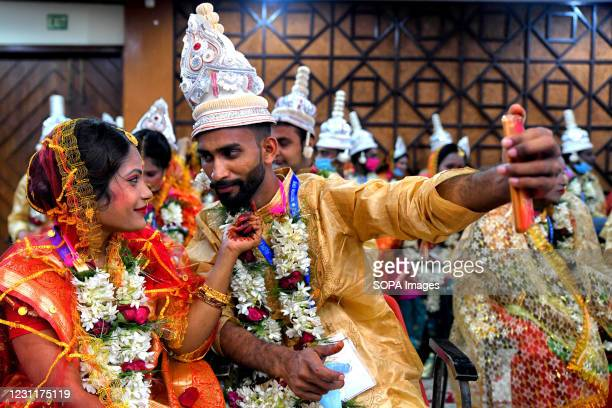 """Couple takes a selfie during the Mass Marriage ceremony. An NGO called """"Aloy Phera"""" organised a Mass marriage ceremony of 70 Couples from different..."""