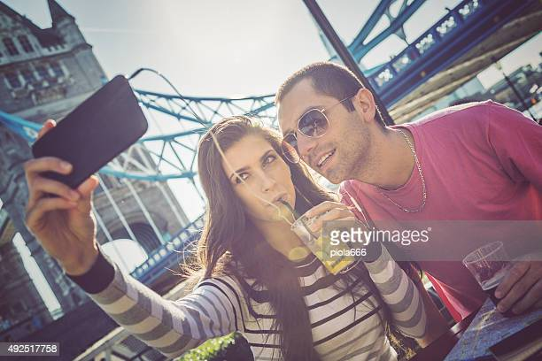 Couple takes a selfie in front of Tower Bridge