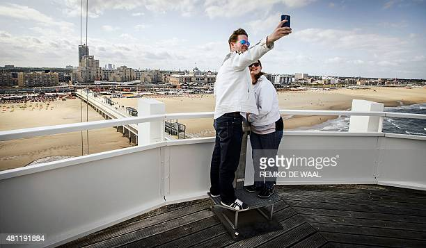 A couple takes a selfie on the pier at the beach of the Dutch resort town of Scheveningen near the Hague on July 18 2015 The landmark was bought by...