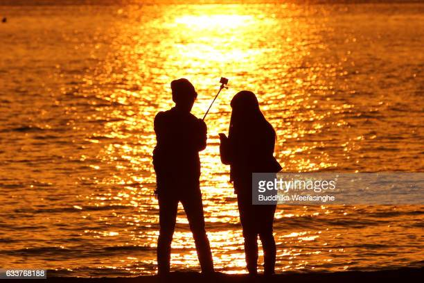 A couple takes a selfie photo as they enjoy during the first day of spring during sunset at the Shinmaiko beach on February 4 2017 in Tatsuno Hyogo...