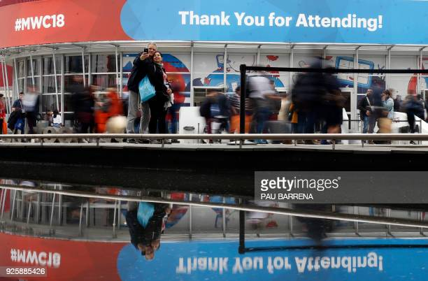 A couple takes a selfie photo outside the venue of the Mobile World Congress on the last day of the world's biggest mobile fair on March 1 2018 in...